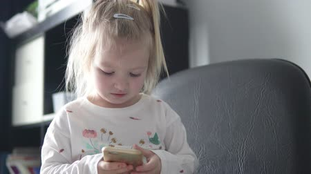 Beautiful little girl holding a mobile phone in her hands and looking at the screen. Close-up baby. She sits in a chair, laughs and presses the screen of the phone.