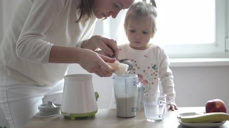 Mom and little daughter are preparing a milkshake. They put ice cream in a blender. A little girl puts a spoon of ice cream on a spoon and feeds her mother with leftovers. They are happy they have fun