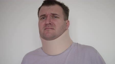 A man with severe pain in the neck. He has a medical fixture around his neck. He writhes in pain