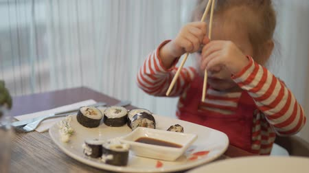 A little girl eats sushi. She takes a piece of roll with wooden chopsticks, dunk into a sauce and chews deliciously. Dostupné videozáznamy