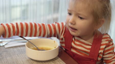The little girl eats vegetable soup. She sits at the table and holds a spoonful of soup, brings it to her mouth and eats. Then she wipes her face with a paper napkin.