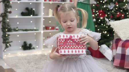 Beautiful elegant woman gives New Years gift to a little girl. Elegant baby takes a box, moves away from the Christmas tree and opens it. She is glad to present. Mom and daughter in Christmas at the