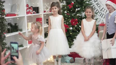 A woman photographs elegant children at a Christmas party. Mom makes a photo on the phone of little girls in lush dresses and a boy in a suit, he gives the sisters a gift at the Christmas tree