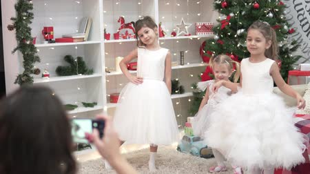 A woman photographs elegant children at the Christmas tree. Cute sisters in lush dresses posing for mom in the Christmas room Stock Footage