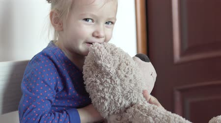 A cute little girl is hugging a gray teddy bear. Stock Footage