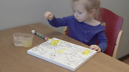 Little girl paints a picture. The child is sitting at the table, in front of her is a canvas with painted ducks and a pond. She draws yellow paint
