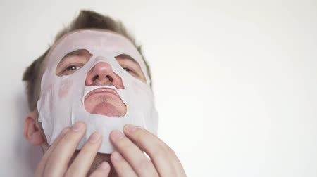 A man applies a moisturizing mask to his face. He smoothes the mask with his fingers over his face, it turns out awkwardly