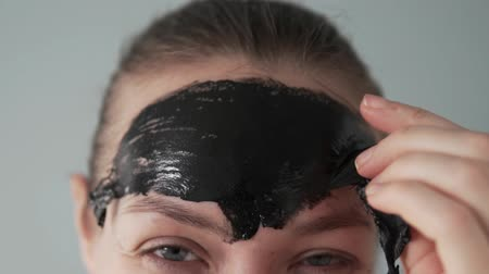 čelo : A woman removes the remains of a black film mask from her forehead. Close-up, slow motion. Dostupné videozáznamy
