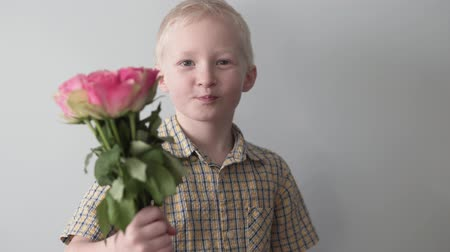 conserva : A blond boy pulls out a bouquet of pink roses from behind and pulls them into the camera. The child smiles and sends a kiss. Little romantic lover Stock Footage