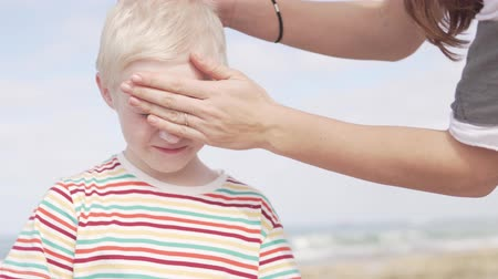 preocupações : Mom smears the face of an albino boy with sunburn protection cream. Family on the beach does sunscreen