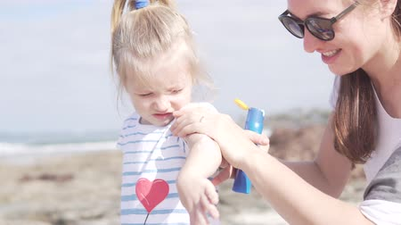 preocupações : Mom and daughter came to the beach. Woman smears sunscreen the hand of a little girl. Babys skin is light Stock Footage