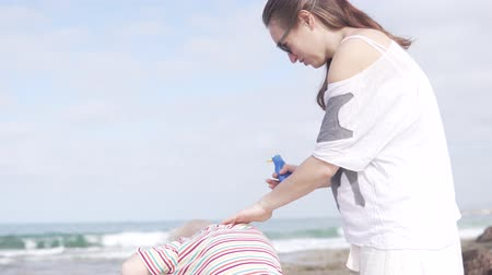 preocupações : Woman smears the childs neck with sun protection cream. The boy is scrappy, he begins to twitch. They stand near the sea, on the beach is hot and sunny