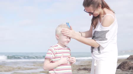 preocupações : Mom smears her son blond to protect against sunburn. Woman applying protective cream on baby albino face Stock Footage