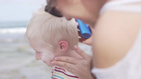 preocupações : Mom smears the face of an albino baby with sun protection cream. Close-up. She smears white cream on the boys white cheeks. Stock Footage