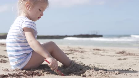searches : Cute little girl sitting on the sandy beach by the sea. The child buries its feet with sand. She diligently plays her game