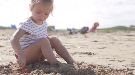 searches : Cute little girl sitting on the sandy beach by the sea. Rebbenok buries his feet with sand. Girl holding a red shovel and digging sand