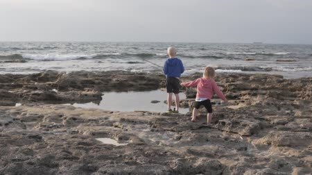 kum saati : A boy and a little girl are walking along the rocky shore towards the sea. Slow shooting