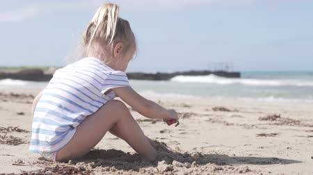 striptiz : Beautiful girl playing on the sandy beach by the sea. The sea is not calm, a lot of waves. The child buries its feet with sand. She diligently plays her game Stok Video