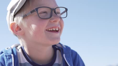 regozijo : Handsome blond boy laughing merrily. The child tells the story and smiles. albino closeup on walk. his body is as closed as possible from the sun Stock Footage