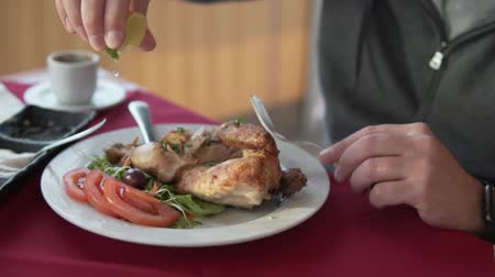 fürj : Male hand squeezes lime juice on smoked chicken. A drop of lemon juice slowly fall on the dish. Food decorated with tomatoes and cucumbers Stock mozgókép