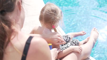 preocupações : Mom smears her daughters back cream. The child sits at the pool with a bare back Stock Footage