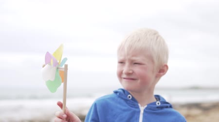 szeplők : Boy blond is holding a windmill toy. The child turns the toy, so that her shovels spin in the wind. The boy smiles and plays a color toy on a stick