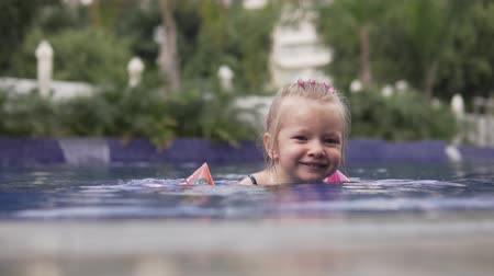 plavec : Happy little girl swims in the pool in armbands. Baby smiles and swims in the direction of the side. Beautiful little girl blonde swims alone in the pool Dostupné videozáznamy