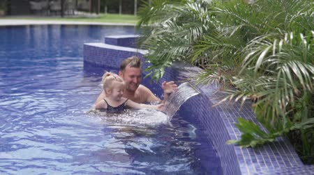 pólos : Dad with a little daughter swim in the pool. A man and his daughter look at the fountain in the pool and touch the water. Dad teaches a child to swim. Relax at the hotel by the p Stock Footage