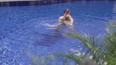 nadador : Dad with a little daughter swim in the pool. A man plays with a baby in an outdoor summer pool. Holidays with a child in Cyprus. Family teaches daughter to swim