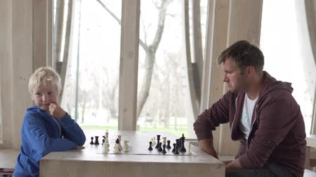 delikanlı : Dad and son play chess in a chess club. A blond man and boy are sitting at a wooden table by a large window and playing chess. Boy makes a move Stok Video