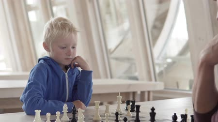 akutní : Dad and son play chess in a chess club. The guys are sitting at a wooden table, the boy makes a move. Chessboard standing on a table at a large bright table Dostupné videozáznamy