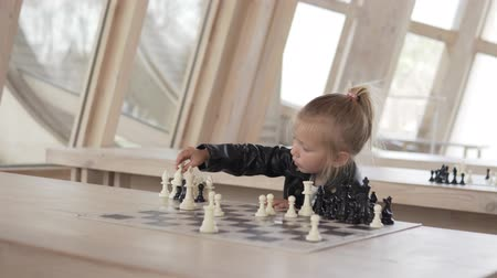 taranmamış : Beautiful little girl playing chess. The baby gently removes the pieces from the chessboard. a girl sits at a wooden table by a large window and puts the figures aside Stok Video