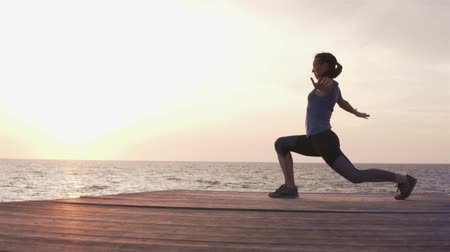 apertado : Woman doing fitness workout at sunset by the sea. She jumps from one foot to the other and stretches her muscles. Beautiful workout at sunset. She practices on a wooden bridge on a cliff near a cliff.