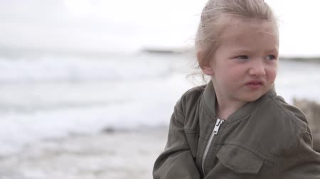 Ванкувер : little girl sitting on the sea shore looking seascape. Alone little girl 2 - 3 years old caucasian blonde in the green jacket at the sea background in cloudy day, the wind rustles