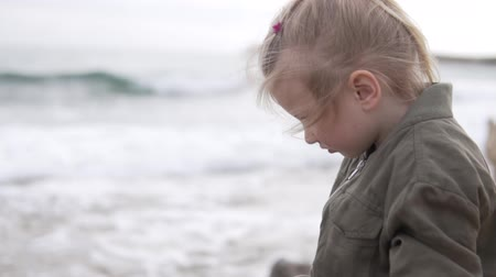 Ванкувер : Beautiful little girl in a jacket looks at the sea. The girl sits on a rock by the ocean and calmly looks at the sky Стоковые видеозаписи