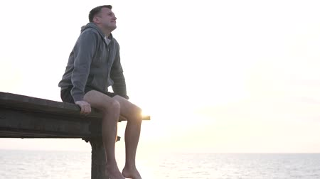 boldness : A man in a sweatshirt is watching the sunset. He sits on the bridge and legs his feet above the abyss with the sea. Happy fat guy on vacation at the ocean. Handsome man after sport training looks at s