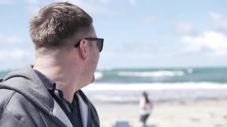 смущенный : A man on the beach looks back at a woman passing by. The man looked at the woman, then embarrassed and laughed