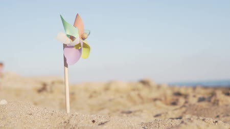 ventilátor : Multi-colored toy windmill stuck in the sand on the beach, it slowly turns from the wind. pinwheel with a blowing wind stands on sand by the sea Dostupné videozáznamy