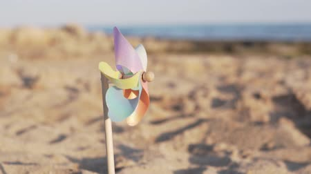 ventilátor : A rotate colored plastic pinwheel with a blowing wind stands on sand by the sea against the smooth surface of the sea and a bright pink sunset. Toy mill on the beach. Dostupné videozáznamy