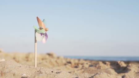 ventilátor : A rotate colored plastic pinwheel with a blowing wind stands on the sand by the sea against the blue smooth surface of the sea and the sunset of the day. Toy mill on the beach. Beautiful pattern