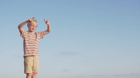 bulutsuz : Happy boy walks on the street. The child on the background of a cloudless sky jumps and gesticulates with his hands