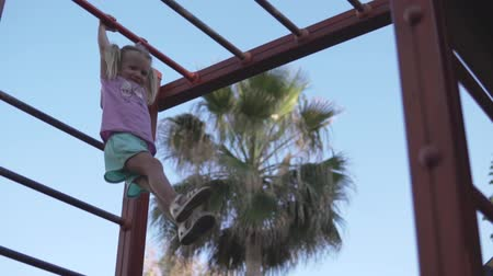 climbed : A sports little girl climbed onto the top of the stairs in the playground. Baby laughs and hangs high above the ground on the crossbar. Little girl hang on sports rings at playground