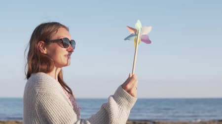 tiller : Beautiful woman in sunglasses on summer holiday playing with toy windmill. A woman stands on the beach, she is holding a toy tiller in her hands. The colored blades swirl beautifully in the wind
