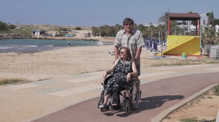 arch rock : An elderly man carries a woman in a wheelchair along the sea. The husband carries his wife with a broken leg in the wheelchair past the window. A woman with a broken leg in an orthosis in a wheelchair