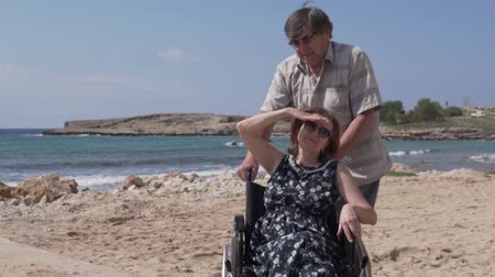 değil : An elderly man carries his wife in a wheelchair along the promenade along the sea. An old woman with an orthosis on her leg looks out over the ocean. Wheelchair Holidays in Cyprus Stok Video
