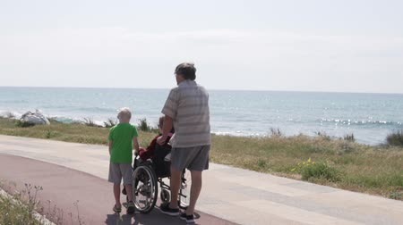 甘さ : a man with a boy carry a wheelchair with his grandmother along the coast. Disabled family walking near the sea. Convenience for holidaying people with disabilities in Cyprus