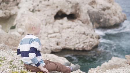 smutny : A handsome blond boy throws stones at sea. The child sits on the edge of a cliff and looks at the sea. A boy who is 7 years old sits by the sea Wideo