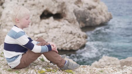 admires : beautiful blond boy sitting on a cliff and rocks by the sea. The child dreamily looks into the distance towards the ocean. Beautiful, romantic video