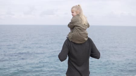 observação de pássaros : A little girl sits on the shoulders of her father and looks at the sea. A child in a jacket looks at the ocean on the shoulders of a man. The man turns and they smile