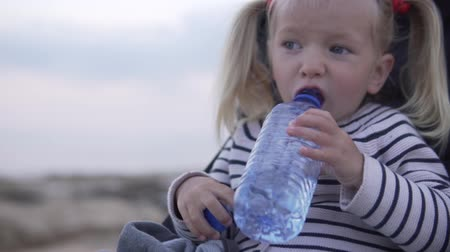 sede : Blond Little girl drinking water from a plastic bottle in the summer park. the baby is sitting in a stroller and opens a mug on a bottle of water. Behind the child a beautiful sunset in the sea